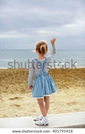 Little girl in a striped denim dress standing back and waving goodbye on a background of sea and sand in the summer - stock photo