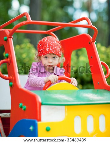 Little girl in a toy car cabin - shallow DOF - stock photo