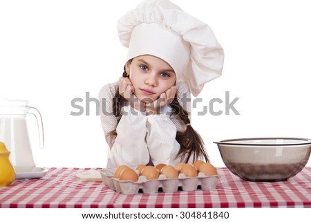 Little girl in a white apron near the box with eggs, isolated on white background