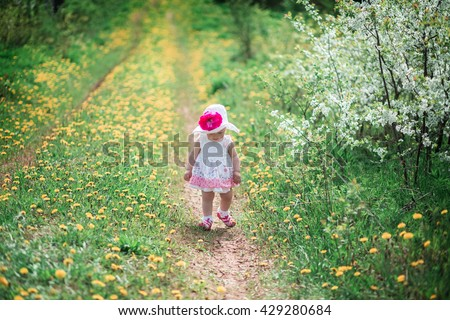 Little girl in a white dress and a hat on the track with flowers