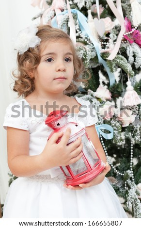 little girl in a white dress holds a lamp in hand near a Christmas fir-tree