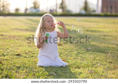 little girl in a white dress on the lawn blow bubbles - stock photo