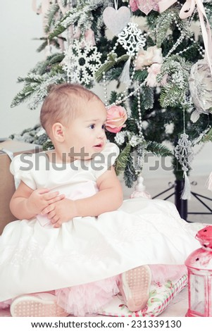 Little girl in a white dress  sits  near a Christmas fir-tree - stock photo