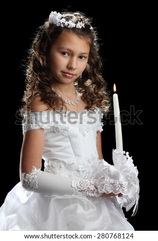 little girl in a white, fluffy dress. with a candle in hands. charming smile. first communion. - stock photo