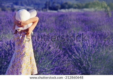 Little girl in a white hat looking at the lavender field - stock photo