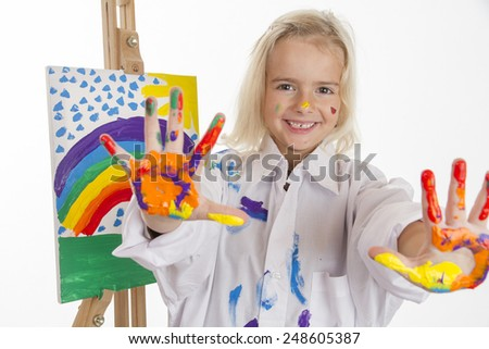 Little girl in a white robe painted a rainbow