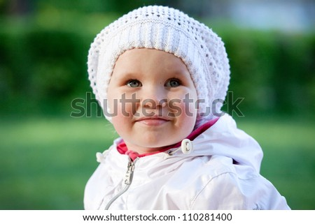 Little girl in a white suit and knitted cap