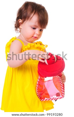 little girl in a yellow dress, played with a red toy. isolated on white - stock photo
