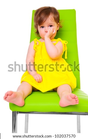 little girl in a yellow dress sits on a green chair. child-focused. isolated on white. studio photo
