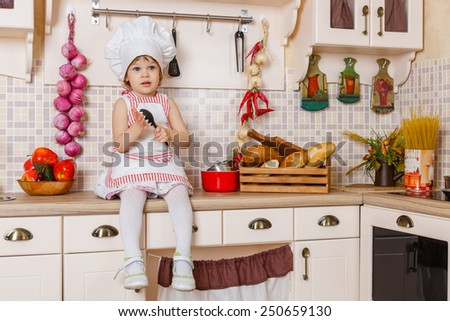 Little girl in apron and cap of the cook sits in the kitchen in the house. Mother's helper. 2 year old. - stock photo