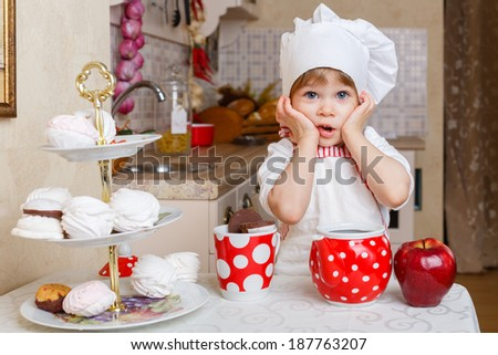Little girl in apron and cap of the cook with sweet desserts sits at the dining table in the kitchen in the house. Mother's helper. 2 year old.