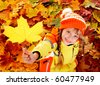 Little girl in autumn orange leaves. Outdoor. - stock photo