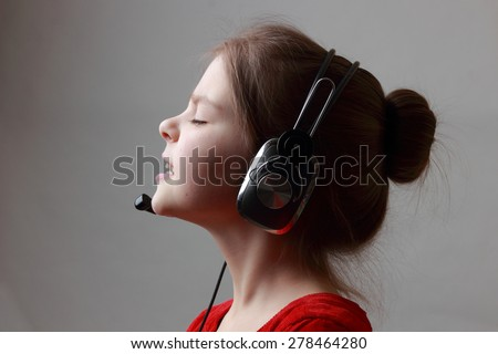 Little girl in beautiful red dress singing with headphone - stock photo