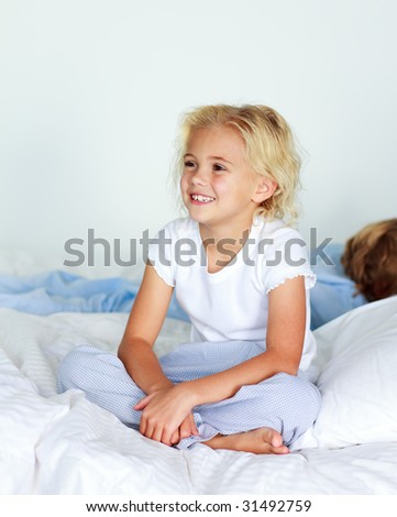 Little girl in bed smiling while her little brother is sleeping