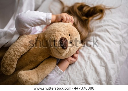 little girl in bed with soft toy the emotions of a child - stock photo