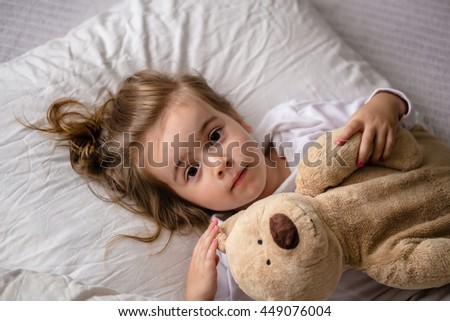 little girl in bed with soft toy the emotions of a child, white bed - stock photo