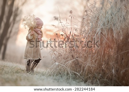 little girl in beige coat and hats standing near the tall grass covered with frost on the nature at sunset at winter time  - stock photo
