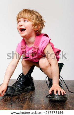 little girl in big boots having fun standing on the table  - stock photo