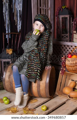Little girl in big size sweater, scarf and beret with a green apple in his hand sitting on a barrel and looks sad in the picture