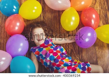 little girl in birthday party lying on wooden floor with rainbow balloons. - stock photo