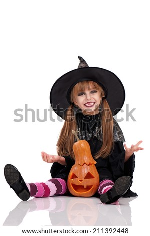 Little girl in black hat with pumpkin sitting on floor, isolated on white background