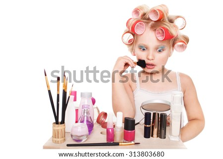 Little girl in blond hair curlers and makeup isolated on white background space for inscriptions - stock photo