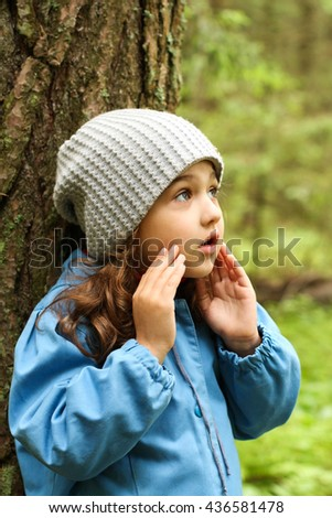 Little Girl In Blue Coat With Sad Expression On Face In Forest.