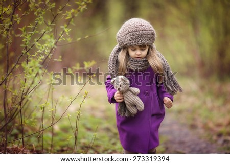 little girl in brown hat and scarf and purple coat is walking in the park with her toy teddy bear her hand at spring time - stock photo