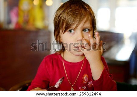 little girl in cafe licking her fingers after meal - stock photo