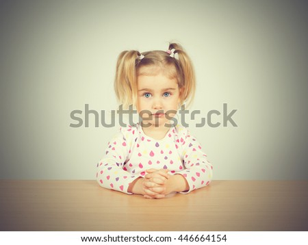 Little girl in casual clothes looking up and thinking. Sitting at the table. - stock photo