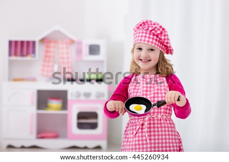 Little girl in chef hat and apron cooking fried eggs in toy kitchen.  Wooden toys for young children. Kids play and cook at home or daycare. Toddler kid playing with stove, tableware, pans and dishes. - stock photo