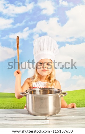 Little girl in chef hat cook healthy soup in a big pot, and prepares the dough for dumplings, pizza, using a wooden rolling pin - in the open air on the background of the solar sky  - picnic - stock photo