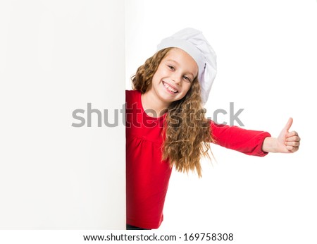 little girl in chef hat with a white board shows thumbs up - stock photo