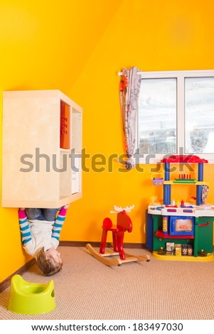 Little girl in children room sitting at the shelves upside down at inverted house
