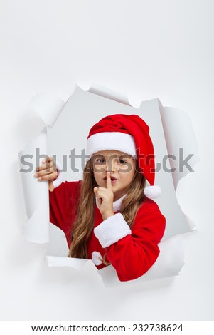 Little girl in christmas outfit telling you a secret - leaning out of a jagged edge hole - stock photo