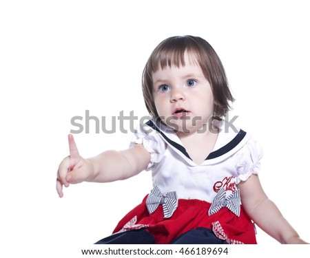 Little girl in colorful dress. Point a finger. Isolated on white background.