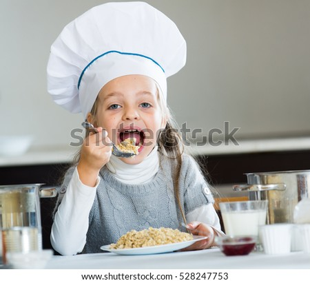 Little girl in cook hat with milk and oatmil kasha