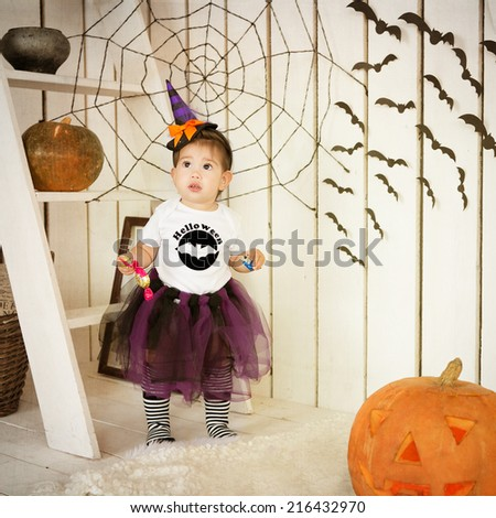 Little girl in costume Halloween witch on a holiday - stock photo