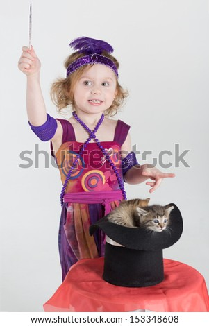 Little girl in costume magician waves her wand over the cylinder with kittens - stock photo