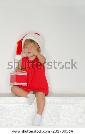 little girl in costume of Santa sitting on fireplace