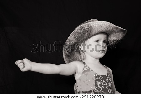 Little girl in cowboy hat pointing with her arm - stock photo