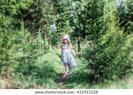 Little girl in dress and hat standing on a footpath in the woods