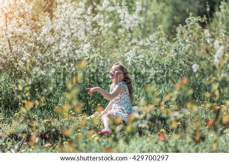 Little girl in dress on the background of a flowering tree playing with a butterfly