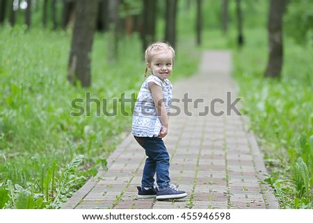 Little girl in fear standing on the road in park