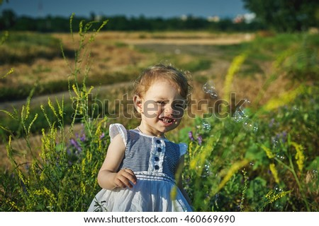little girl in field with wildflowers