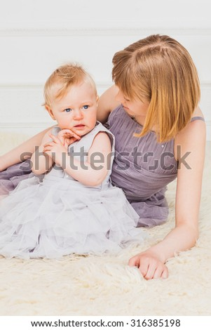 Little girl in  fine dress  sitting with her older sibling