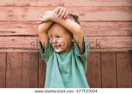 Little girl in front of a wooden wall