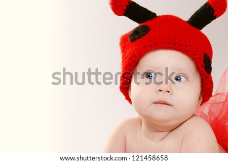 Little girl in funny hat with comic facial expression - stock photo