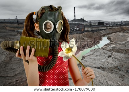 little girl  in gas mask, smell big white flower - stock photo