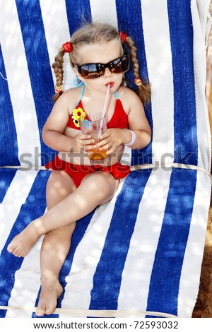 Little girl in glasses and red bikini drink orange juice. - stock photo